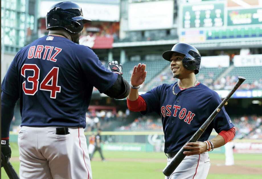 David Ortiz (34) congratulates Mookie Betts after he scored from third base on a Dustin Pedroia single in the first inning on Friday. Photo: Pat Sullivan — The Associated Press  / Copyright 2016 The Associated Press. All rights reserved. This material may not be published, broadcast, rewritten or redistributed without permission.