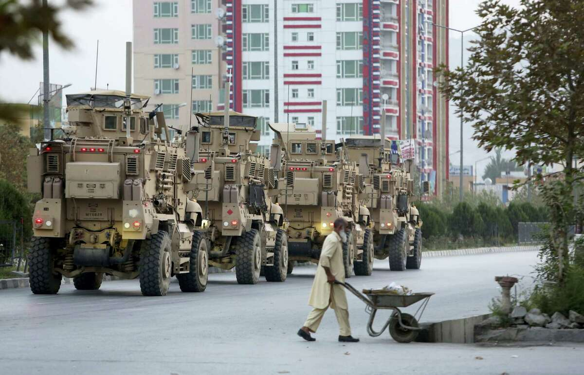 Military vehicles guard after an attack on the American University of Afghanistan in Kabul, Afghanistan, Thursday, Aug. 25, 2016. The attack has ended, a senior police officer said Thursday, after several people were killed. Kabul police Chief Abdul Rahman Rahimi said the dead included one guard, and that about 700 students had been rescued.