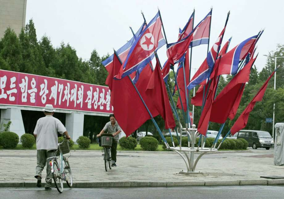 "A North Korean rides a bicycle past national flags flown to mark the celebration of the Songun Day or ""Military First"" holiday in Pyongyang, North Korea, Thursday, Aug. 25, 2016. North Korea marked its ""Military First"" holiday on Thursday with mass dancing, outdoor concerts and boasts of a successful ""and potentially game-changing"" submarine-launched ballistic missile test it hopes will serve as a warning to Washington and Seoul to stop holding joint military exercises Pyongyang sees as a dress rehearsal for invasion. Photo: AP Photo/Dita Alangkara   / Copyright 2016 The Associated Press. All rights reserved. This material may not be published, broadcast, rewritten or redistribu"