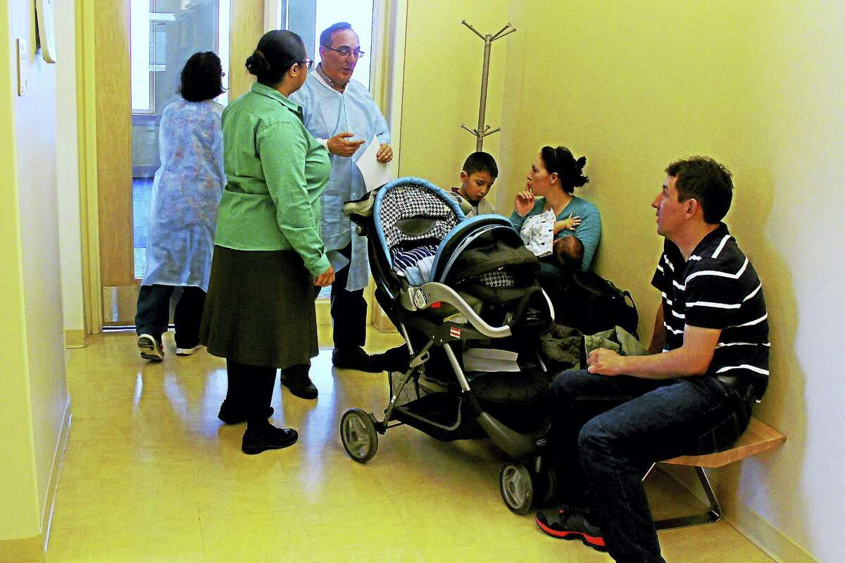 Dr. Michael Mark works with a translator to speak to a young family about their son's dental exam on Tuesday in Middletown.