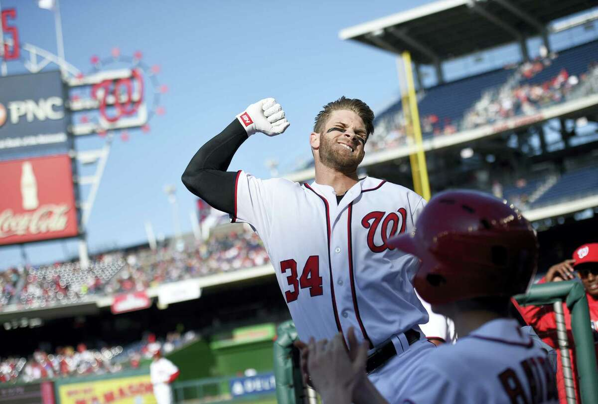 Washington Nationals' Bryce Harper pumps his fist as he takes a curtain call after he hit a grand slam during the third inning of a game against the Atlanta Braves April 14. It was Harper's 100th career home run.
