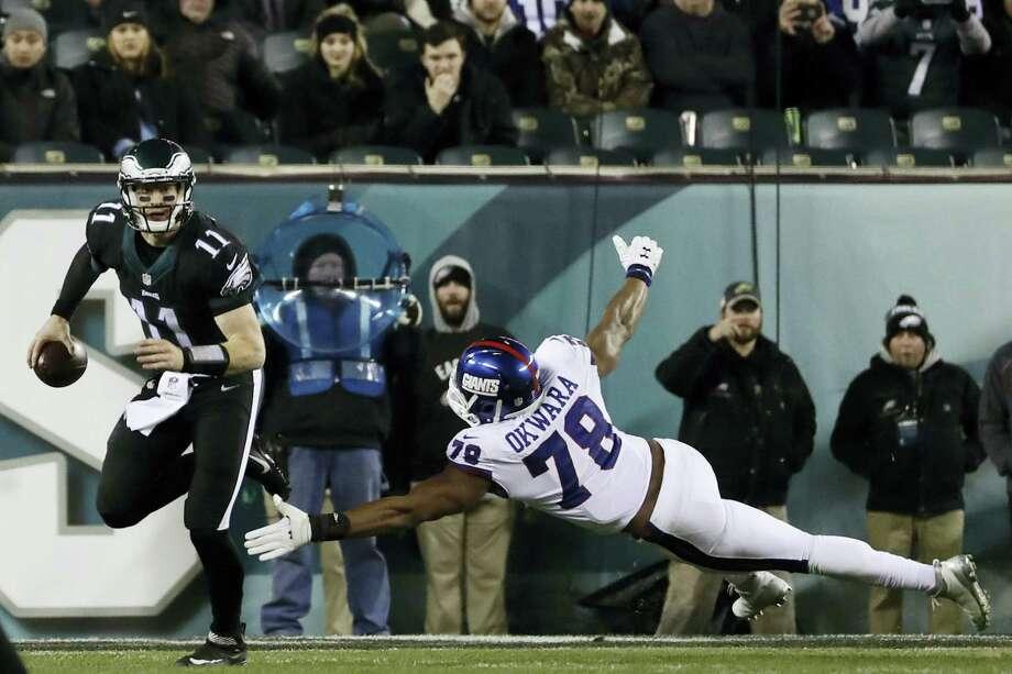 Philadelphia Eagles' Qquarterback Carson Wentz scrambles away from New York Giants' Romeo Okwara during the second half of the Eagles' victory Thursday night. Photo: MICHAEL PEREZ — THE ASSOCIATED PRESS  / FR168006 AP