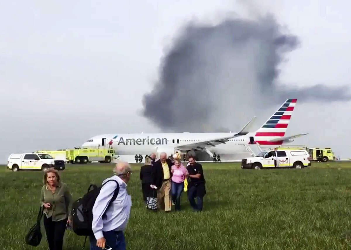 In this photo provided by passenger Jose Castillo, fellow passengers walk away from a burning American Airlines jet that aborted takeoff and caught fire on the runway at Chicago's O'Hare International Airport on Friday, Oct. 28, 2016. Pilots on Flight 383 bound for Miami reported an engine-related mechanical issue, according to an airline spokeswoman.