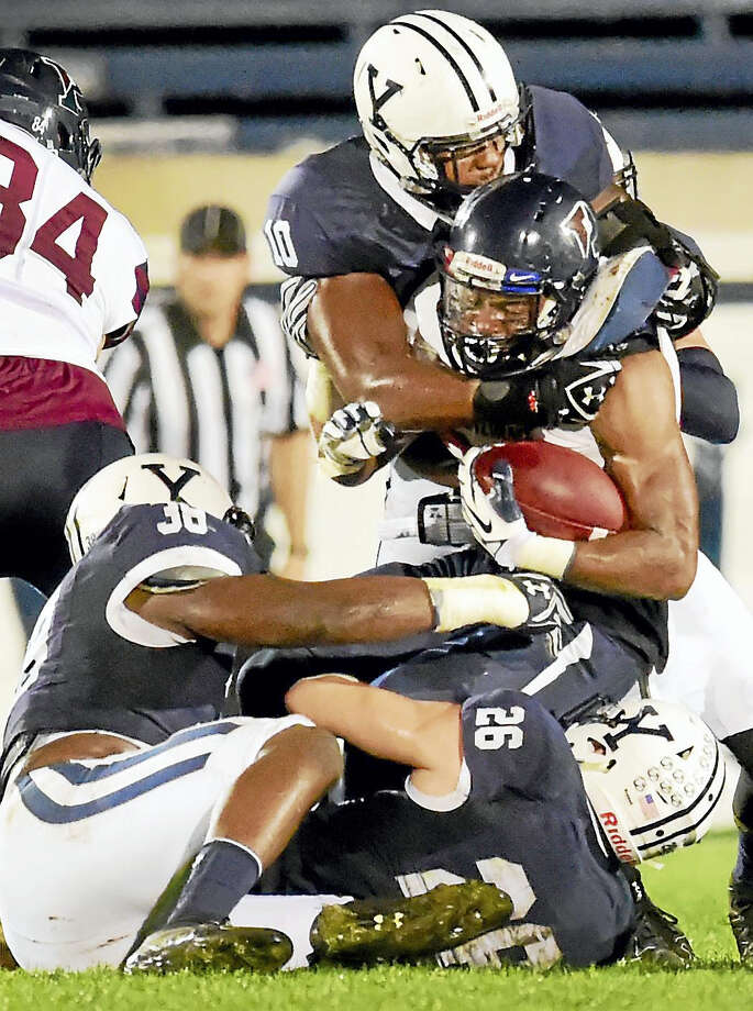 Yale linebacker Victor Egu of wraps up Penn running back Tre Solomon during their game last Friday. Photo: Peter Hvizdak — Register File Photo  / ©2016 Peter Hvizdak