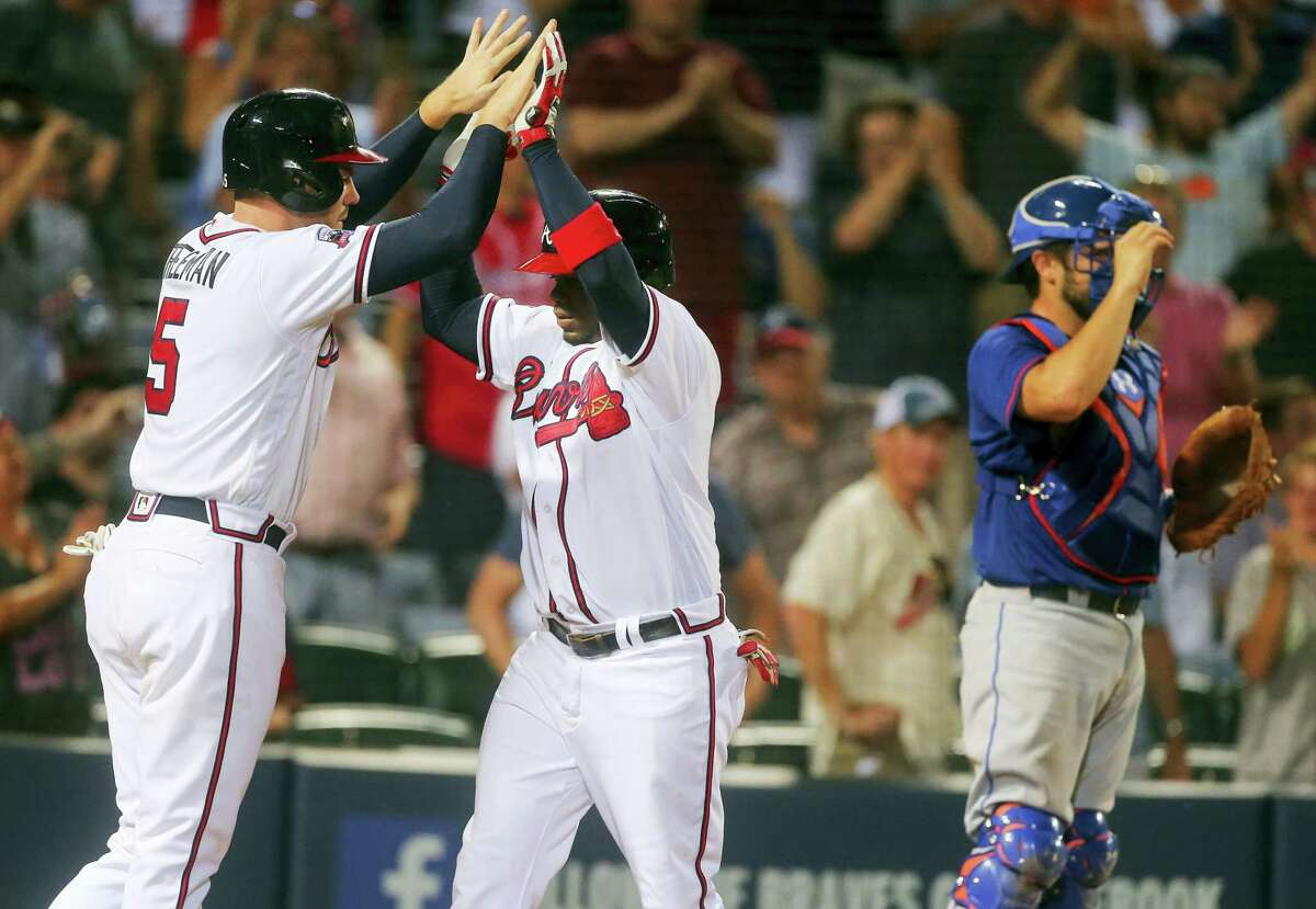 Atlanta's Adonis Garcia, center, celebrates with Freddie Freeman, left, after hitting a two-run home run in the eighth as New York Mets catcher Travis d'Arnaud (7) looks on Thursday. That homer gave the Braves a 4-3 win, the Braves' fourth straight victory over the Mets.