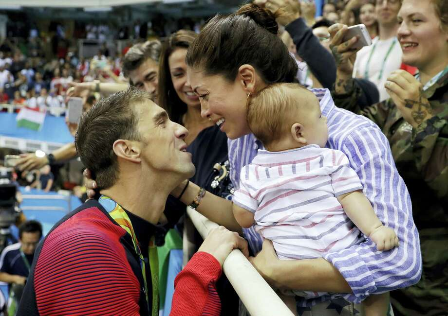 AP Photo/Matt Slocum, File  In this Aug. 9, 2016, file photo, U.S. swimmer Michael Phelps celebrates winning his gold medal in the men's 200-meter butterfly with his wife Nicole Johnson, then thought to be his fiancee, and baby Boomer during the swimming competitions at the 2016 Summer Olympics, in Rio de Janeiro, Brazil. The Arizona Republic reported Oct. 26, 2016, that Phelps and Johnson secretly married on June 13, 2016. Photo: AP / Copyright 2016 The Associated Press. All rights reserved. This material may not be published, broadcast, rewritten or redistribu