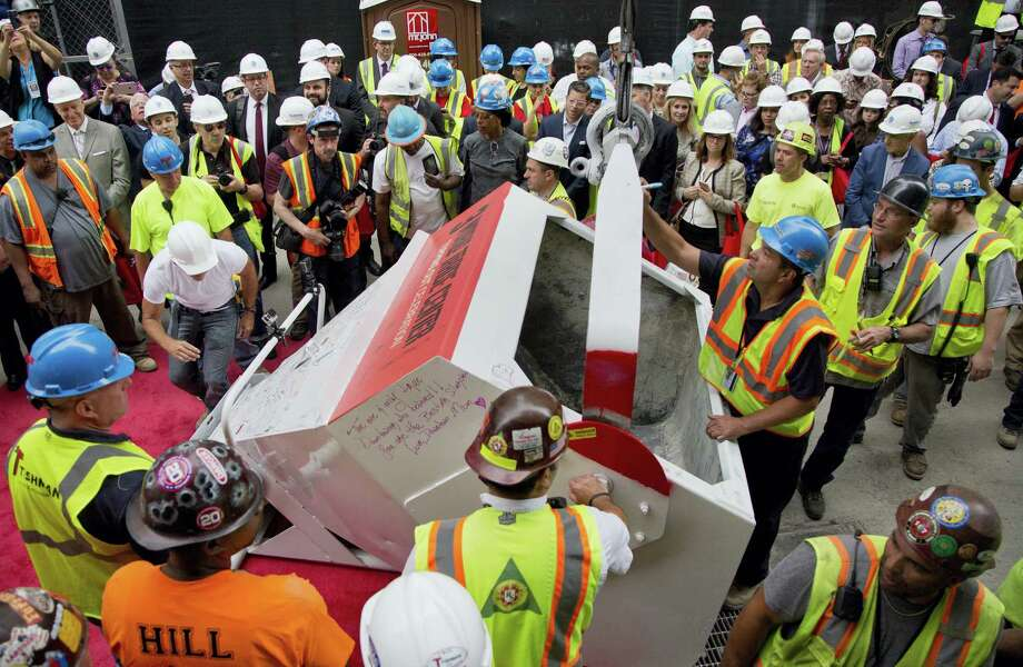 Construction workers gather around to sign a concrete bucket before it is hoisted to the roof of 3 World Trade Center in a topping off ceremony on June 23, 2016 in New York. It's one of three new skyscrapers that replace the twin towers destroyed almost 15 years ago. Photo: AP Photo/Mark Lennihan  / Copyright 2016 The Associated Press. All rights reserved. This material may not be published, broadcast, rewritten or redistribu