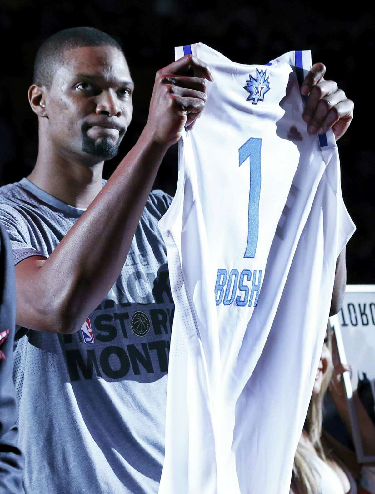 Miami Heat forward Chris Bosh holds up a jersey for the NBA All-Star Game on Tuesday. Bosh will not participate due to a strained right calf.