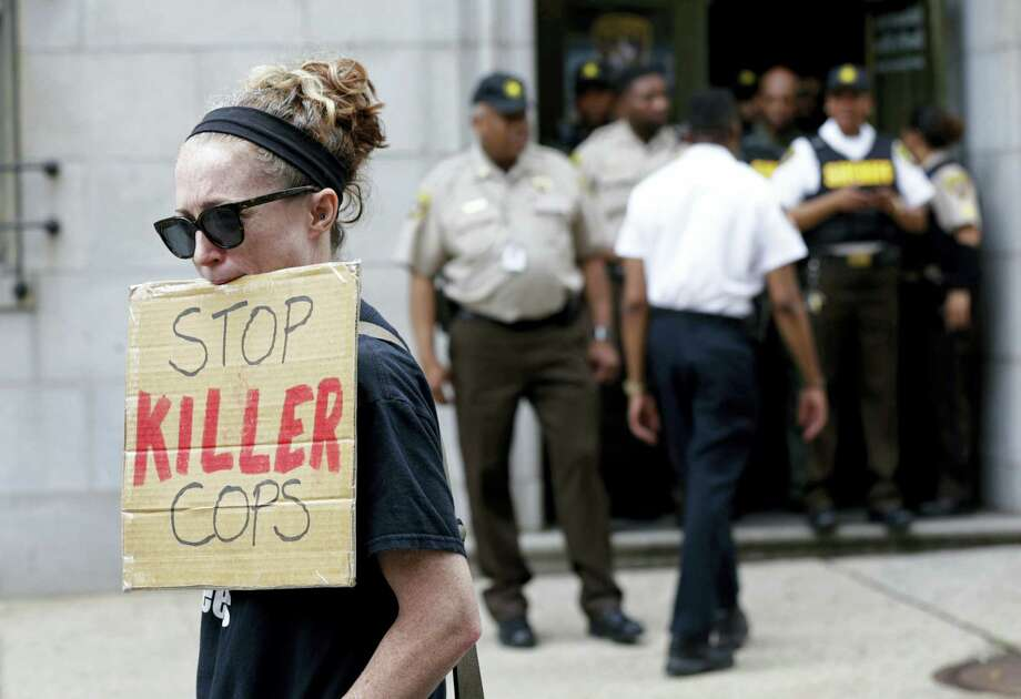 A protester displays a sign outside a courthouse after Officer Caesar Goodson, one of six Baltimore city police officers charged in connection to the death of Freddie Gray, was acquitted of all charges in his trial in Baltimore, Thursday, June 23, 2016. Photo: AP Photo — Patrick Semansky / Copyright 2016 The Associated Press. All rights reserved. This material may not be published, broadcast, rewritten or redistribu
