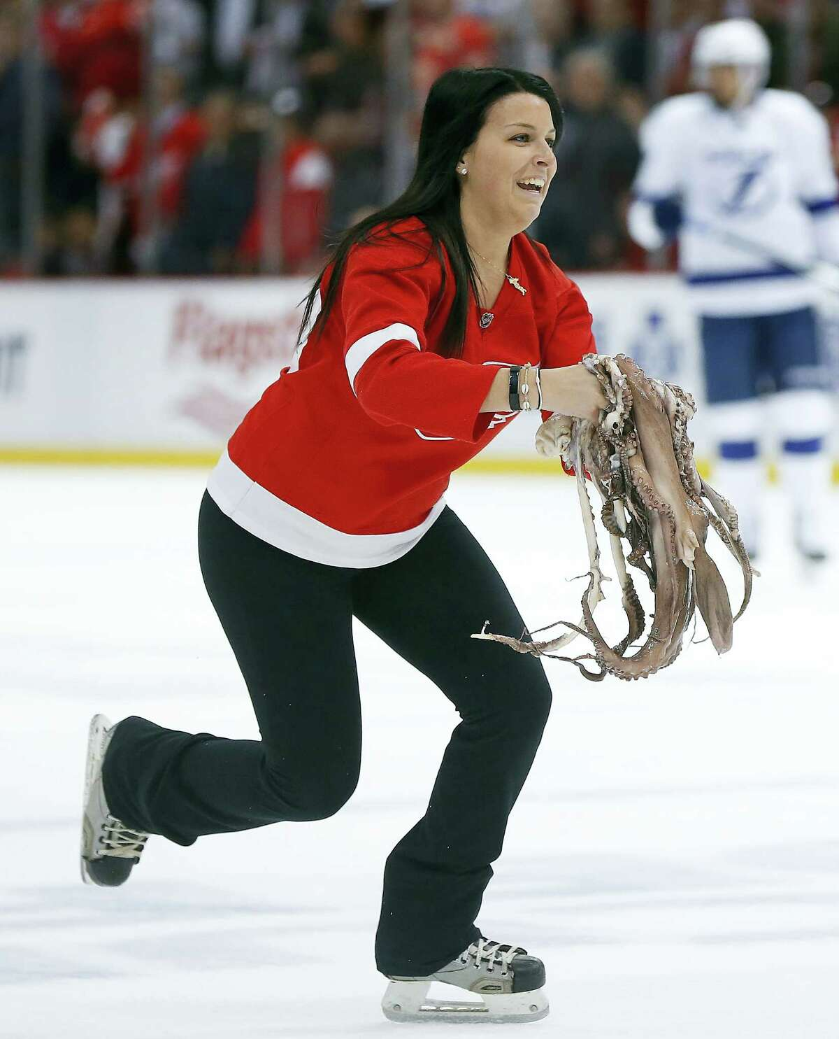 A Detroit Red Wings ice girl removes several octopuses from the ice in the second period of Game 4 of their playoff series against the Lightning.