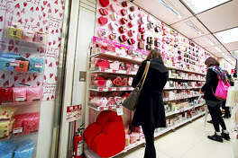 In this Feb. 14, 2012, file photo, women look at heart-shaped boxes containing Valentine's Day chocolates on sale at a store in Tokyo. In Japan, women buy chocolates for men on Valentine's Day, not vice versa.