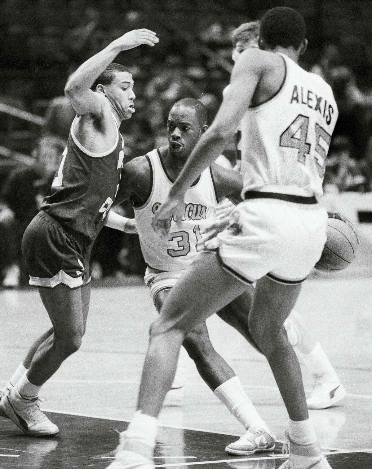 """In this 1986 file photo, Dwayne """"Pearl"""" Washington (31) of Syracuse drives around Boston College's Dana Barros during the Big East tournament."""