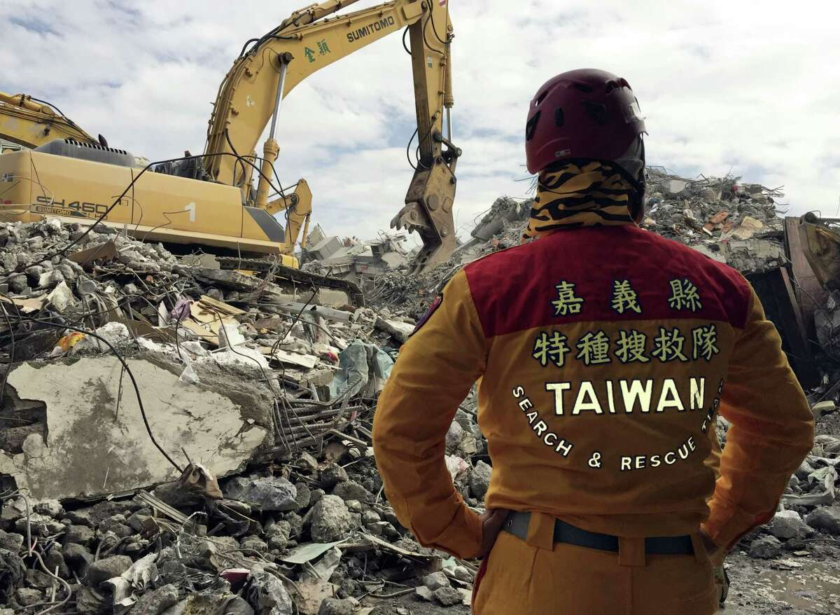A member of rescue teams stands by Thursday, Feb. 11, 2016, as heavy excavation machinery continues to dig through the rubble of a collapsed building complex in Tainan, Taiwan. The Tainan District Prosecutors Office said in a statement Wednesday that they have approved the detention of three construction company executives who are suspected to have overseen shoddy construction of the 17-story Weiguan Golden Dragon building, which tumbled on to its side following an earthquake Feb. 6. Rescue efforts have now ended, Taiwan authorities said Saturday.