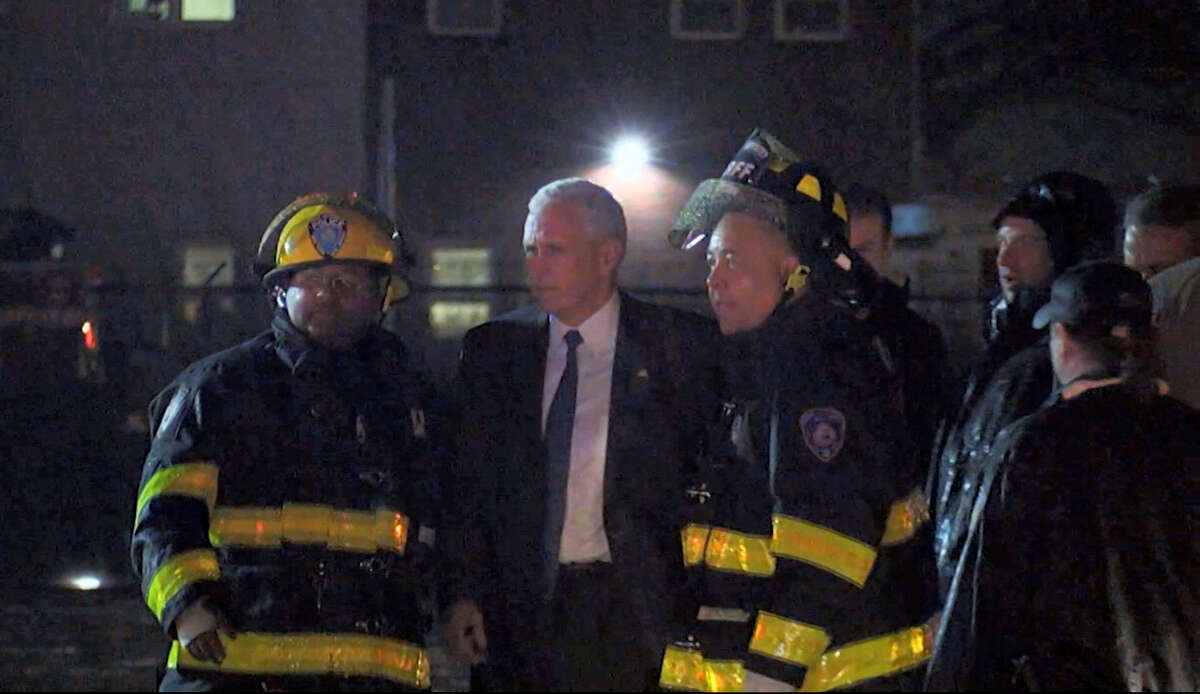 Republican presidential candidate Indiana Gov. Mike Pence talks with firefighters at New York's LaGuardia Airport after his campaign plane slide off the runway while landing on Thursday, Oct. 27, 2016.