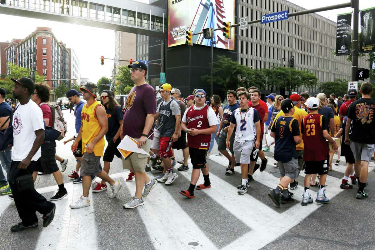 Cleveland Cavalier fans cross the street at the corner of East 9th Street and Euclid to watch a parade celebrating the Cleveland Cavaliers' NBA Championship in downtown Cleveland Wednesday, June 22, 2016.