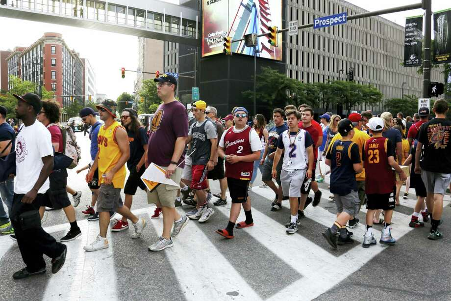 Cleveland Cavalier fans cross the street at the corner of East 9th Street and Euclid to watch a parade celebrating the Cleveland Cavaliers' NBA Championship in downtown Cleveland Wednesday, June 22, 2016. Photo: AP Photo  / AP