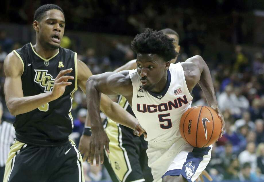 Central Florida's A.J. Davis (3) tries to block Connecticut's Daniel Hamilton (5) as Hamilton drives toward the basket in the second half of an NCAA college basketball game Sunday, March 6, 2016, in Storrs, Conn. Connecticut won 67-46. (AP Photo/Steven Senne) Photo: AP / AP