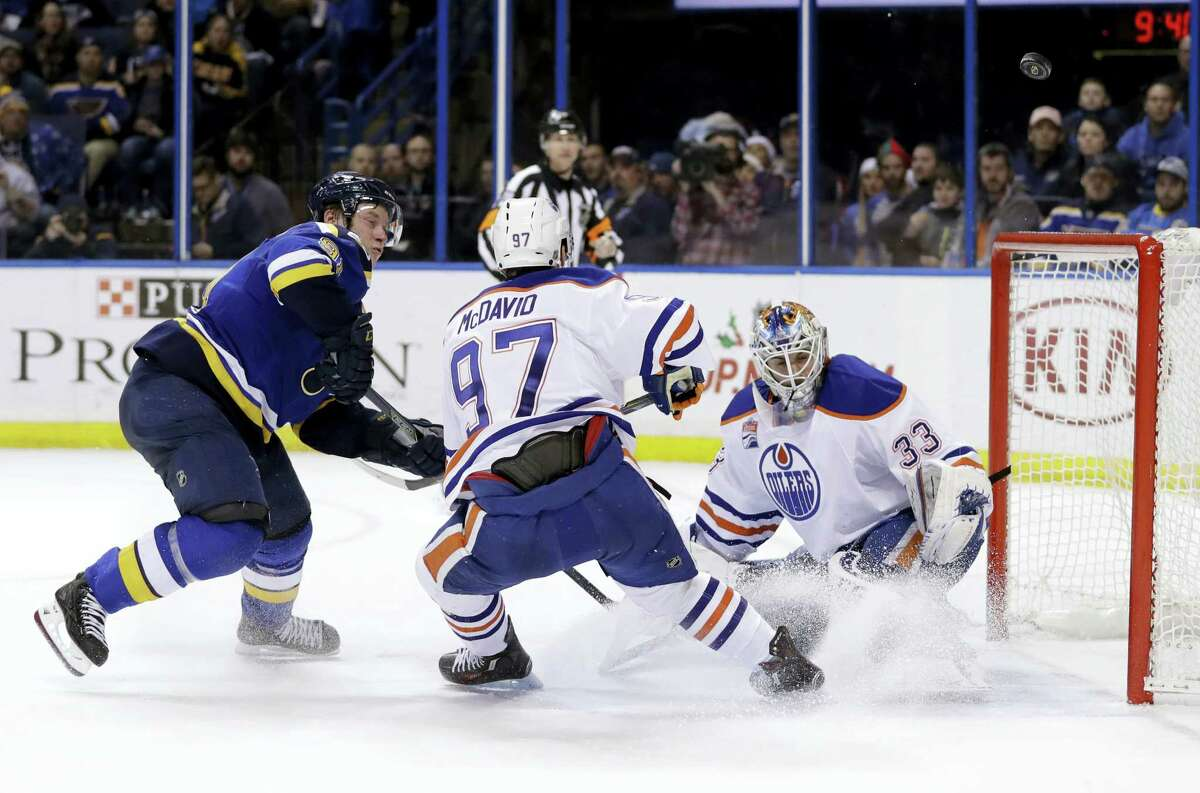 St. Louis Blues right wing Vladimir Tarasenko, of Russia, watches as a puck sails wide past Edmonton Oilers' Connor McDavid (97) and goalie Cam Talbot (33) during overtime of an NHL hockey game Monday, Dec. 19, 2016 in St. Louis. The Oilers won 3-2 in overtime.