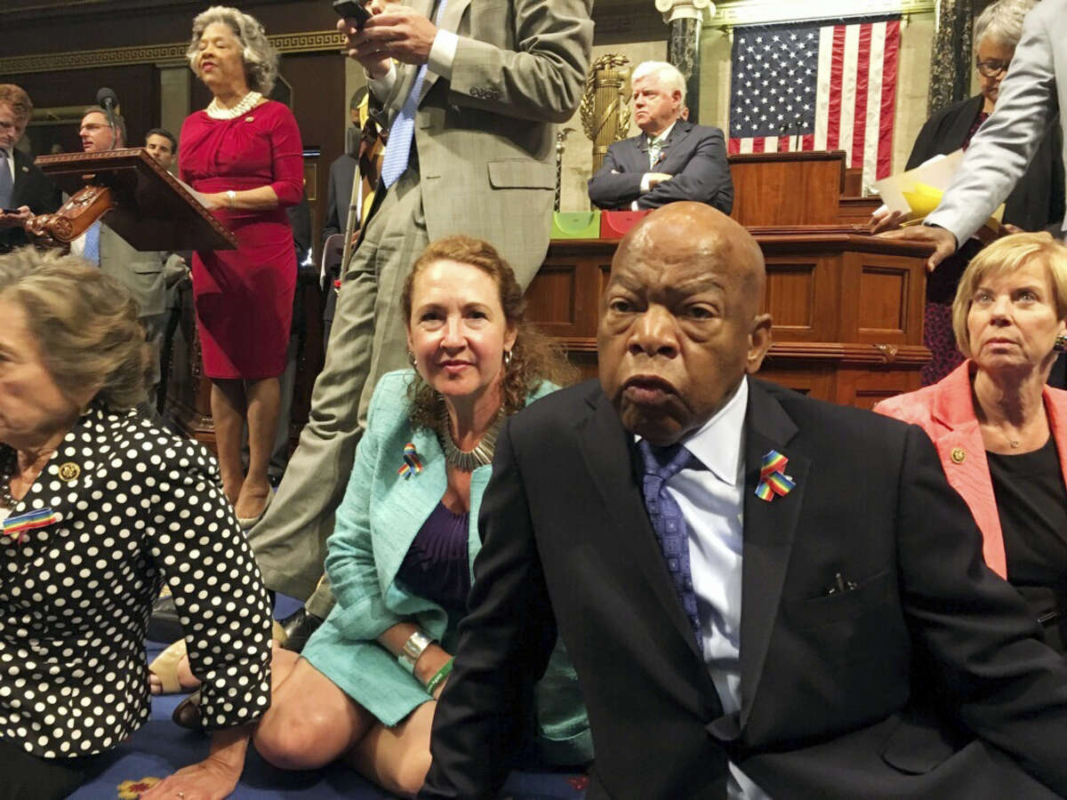 This photo provided by U.S. Rep. Chillie Pingree,D-Maine, shows Democrat members of Congress, including Rep. John Lewis, D-Ga., center, and Rep. Elizabeth Esty, D-Conn. as they participate in sit-down protest seeking a vote on gun control measures Wednesday on the floor of the House on Capitol Hill in Washington.