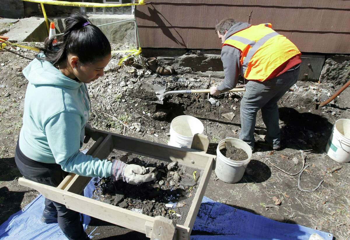 In this March 29, 2016 photo, city archeologist Joseph Bagley, right, digs as volunteer Rosemary Pinales sifts soil for items at the house where slain African-American activist Malcolm X lived for a time with his sister's family in the 1940s in the Roxbury section of Boston, when he was known as Malcolm Little.