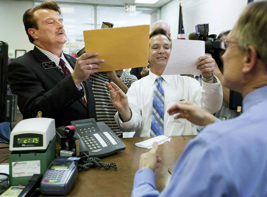 Tony London, left, and his partner, Tim Bostic, center, look at their marriage license paper issued by George Schaefer, right, Norfolk Circuit Clerk of Court, on Monday, Oct. 6, 2014 in Norfolk, Va. London and Bostic, who were plaintiffs in the lawsuit against Virginia's same-sex marriage ban, get the first marriage license issued to them by George Schaefer, Norfolk Circuit Clerk of Court, at the city's Circuit Court. Same-sex marriages began in Virginia on Monday after the U.S. Supreme Court refused to hear an appeal of a lower court decision striking down the state's ban on such unions. Photo: AP Photo/The Virginian-Pilot, The N. Pham  / The Virginian-Pilot