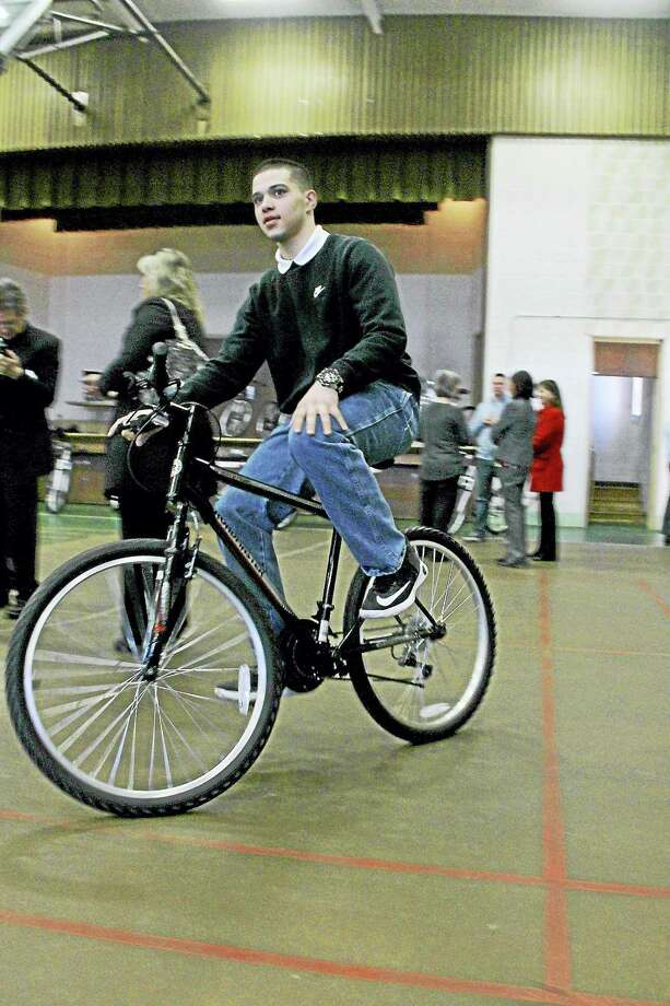 Kathleen Schassler — The Middletown Press Luis, 15, shows some skills riding a mountain bike for a spin in the gymnasium at the Solnit Center in Middletown. Ten bikes were donated by an Old Lyme resident who wished to remain anonymous. Luis is one of two youth from Solnit Center's North campus in East Windsor that came to Middletown to accept the gifts. Photo: Digital First Media / Kathleen Schassler All Rights