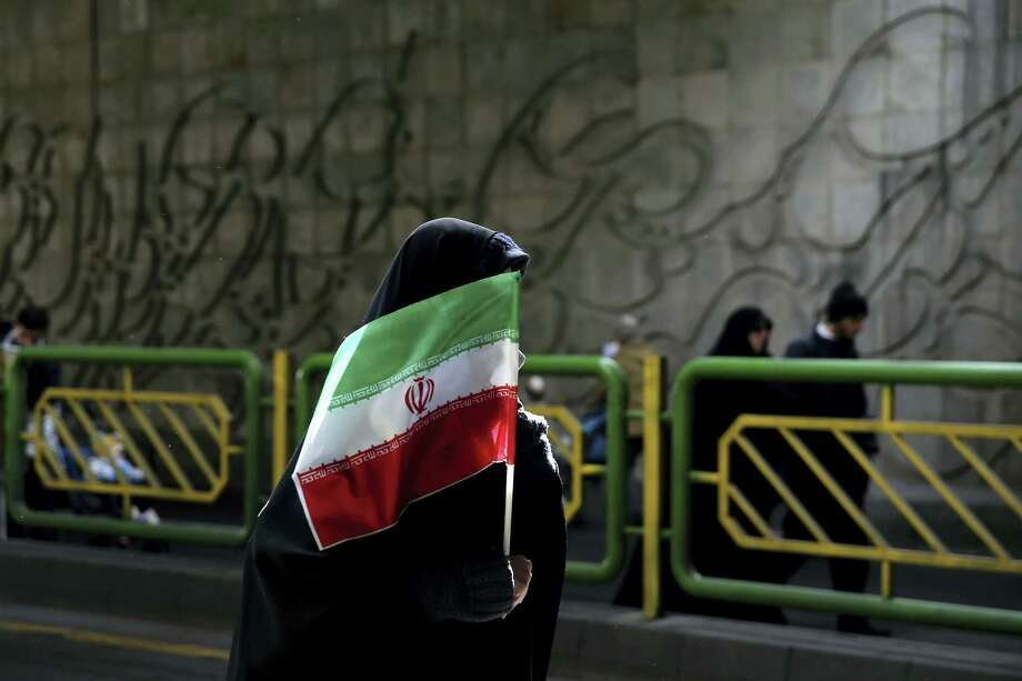 "An Iranian woman holds the national flag during a rally commemorating the 37th anniversary of the Islamic revolution, in Tehran, Iran, Thursday, Feb. 11, 2016. The revolution, on Feb. 11, 1979, saw followers of Ayatollah Khomeini oust the U.S.-backed Shah Mohammad Reza Pahlavi and is celebrated annually. However, Iranians are no longer allowed to celebrate Valentine's Day, which is considered a ""decadent Western"" holiday. Photo: AP Photo/Ebrahim Noroozi   / AP"