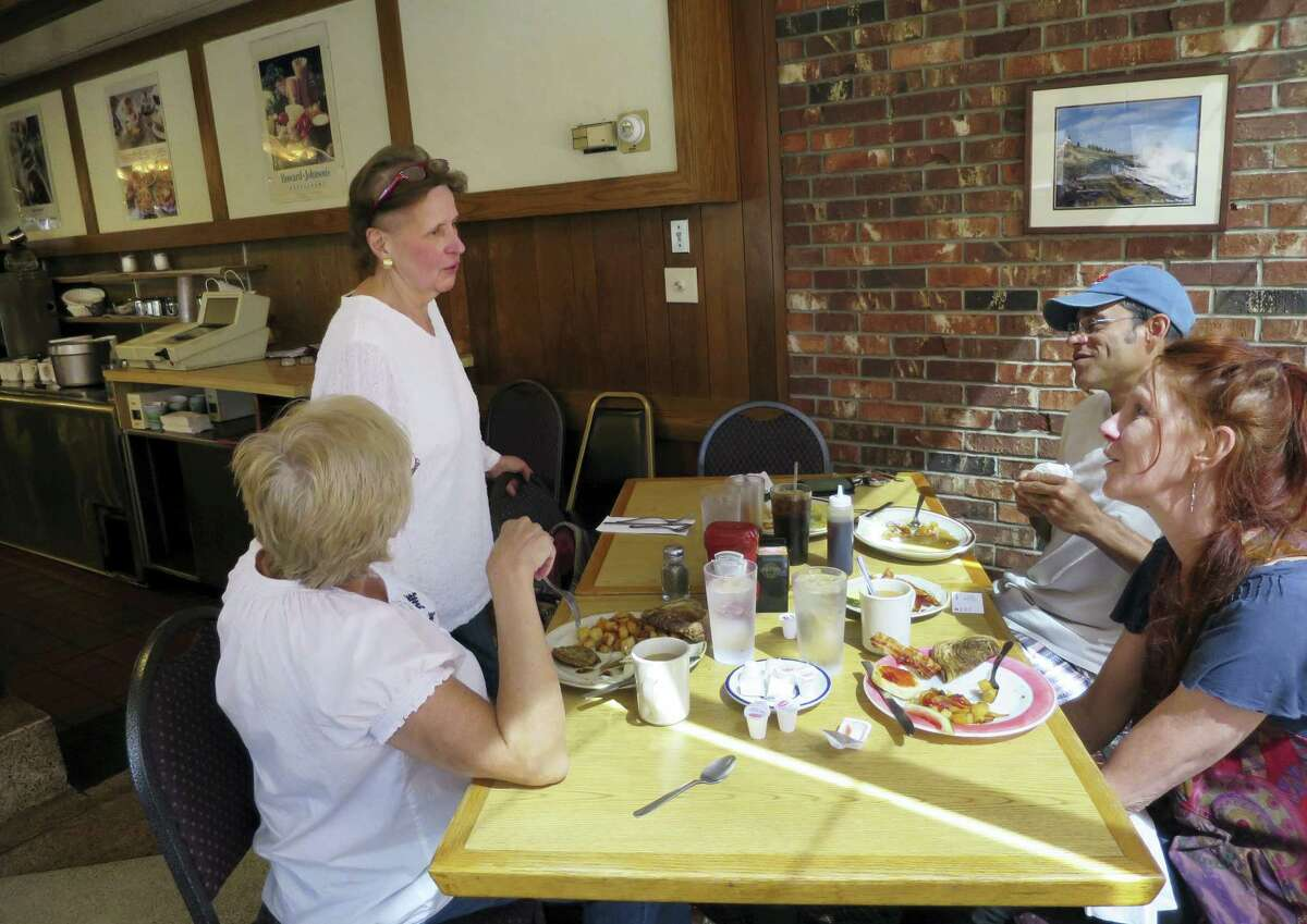 Kathe Jewett, 68, a waitress at Howard Johnson's in Bangor, Maine since it opened in 1966, speaks to patrons, from left, Brenda Astbury, Christopher Leek and Kelly Gill, at the restaurant, Tuesday, Aug. 23, 2016. One of the last two Howard Johnson restaurants will close Sept. 6, 2016, taking with it the fried clam strips, ice cream _ and a slice of roadside Americana.