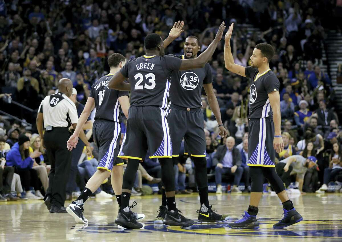 Golden State Warriors' Draymond Green (23), Kevin Durant (35) and Stephen Curry high five each other during the second half of an NBA basketball game against the Portland Trail Blazers Saturday, Dec. 17, 2016 in Oakland, Calif.