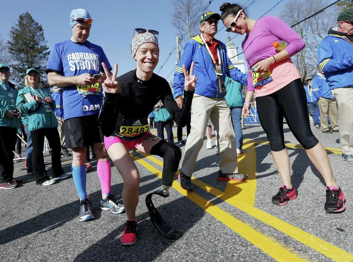 Boston Marathon bombing survivor Adrianne Haslet, center, poses Monday in Hopkinton, Mass., before running the race.