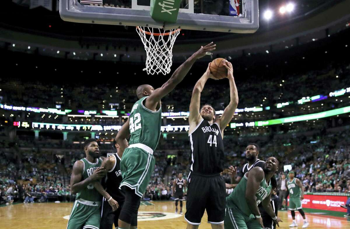 Boston Celtics center Al Horford (42) tries to block Brooklyn Nets guard Bojan Bogdanovic (44) on a shot during the second half of an NBA basketball game in Boston Wednesday. The Celtics defeated the Nets 122-117.