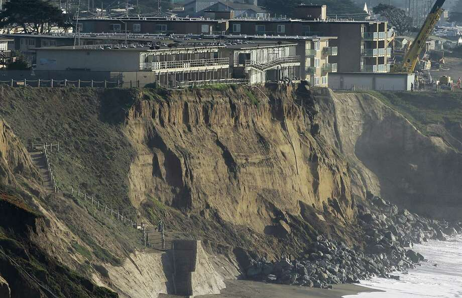 In this Jan. 27, 2016, file photo, boulders shore up an eroding cliff below an apartment complex that residents were forced to evacuate, at top left, in Pacifica, Calif. Living with the Pacific Ocean as your backyard has its benefits. But the crumbling ocean cliffs have forced dozens to move quickly and at a high cost. Photo: AP Photo/Jeff Chiu, File   / AP