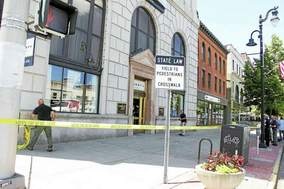 Detectives block off the sidewalk on Main Street near Liberty Bank after a man, who police say was walking to the hospital for treatment, fell down because of injuries suffered during a stabbing at about 1 p.m. Photo: Kathleen Schassler — The Middletown Press  / Kathleen Schassler All Rights