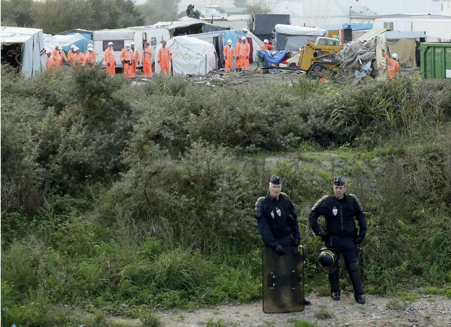 "Riot police take position while crews start to demolish shelters, background, in the makeshift migrant camp known as ""the jungle"" near Calais, northern France, Tuesday, Oct. 25, 2016. Crews in hard hats and orange jumpsuits on Tuesday started dismantling a makeshift camp in France that has become a symbol of Europe's migrant crisis while thousands of people remained there, waiting to be relocated. Photo: AP Photo/Matt Dunham   / AP"
