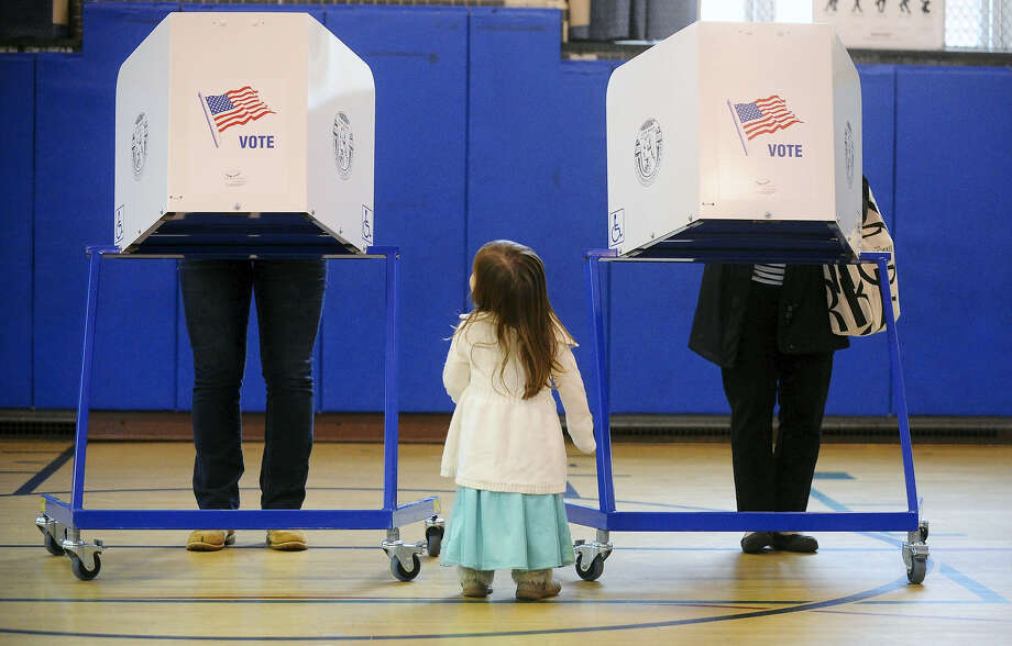 Brigit Mulligan, right, casts her vote as her daughter, Giovanna Candido watches during a primary election at the Sanford St. School in Glens Falls, N.Y. on April 19, 2016. Photo: Steve Jacobs/The Post-Star Via AP  / The Post-Star