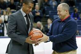 UConn head coach Kevin Ollie, left, is given a ball by athletic director David Benedict to honor his 100th win before Sunday's game in Storrs.