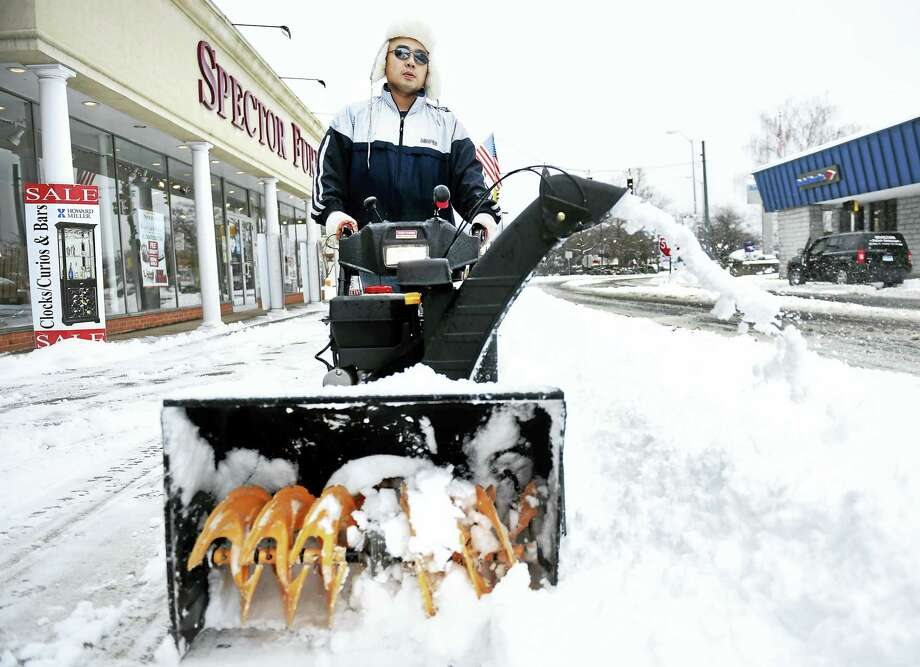 Arnold Gold — New Haven Register Tony Dong clears the sidewalk in front of his restaurant, Koi Sushi & Asian Fusion, on Main St. in Ansonia on 12/17/2016. Photo: Digital First Media