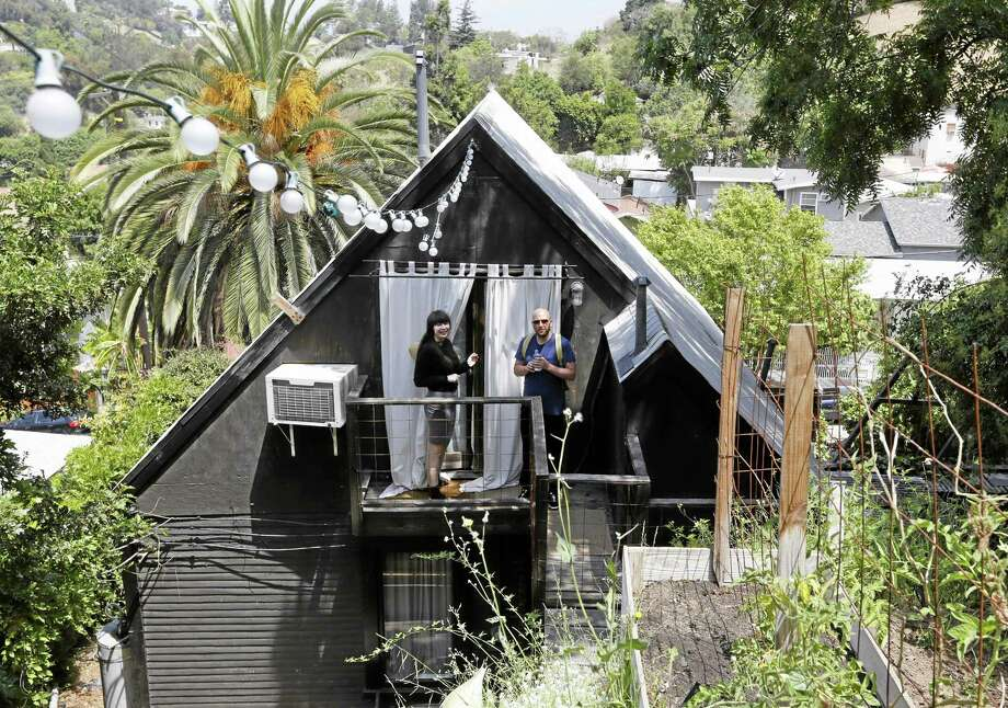 Airbnb guests Camille Smithwick and James Green from Manchester, U.K., pose for photos at an Airbnb property owned by ceramist Jonathan Entler in the Echo Park area of Los Angeles. Photo: AP File Photo — Damian Dovarganes   / AP