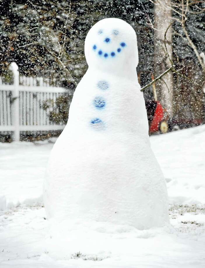 A snowman from a previous storm watches more snow come down earlier this week. Photo: Arnold Gold — File Photo