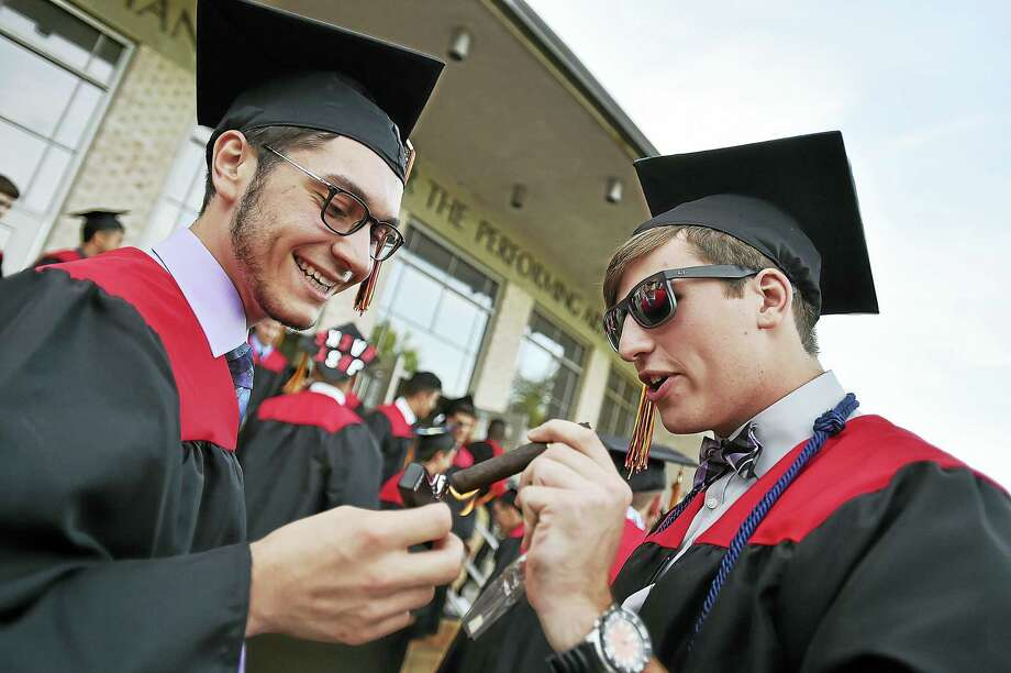 Members of Platt Technical High School class of 2016, Joseph Fraulo and Mike Iozzo light up cigars following ommencement exercises on Wednesday, June 15, 2016 at the John Lyman Center for the Performing Arts at Southern Connecticut State University. Photo: Catherine Avalone/New Haven Register  / New Haven RegisterThe Middletown Press