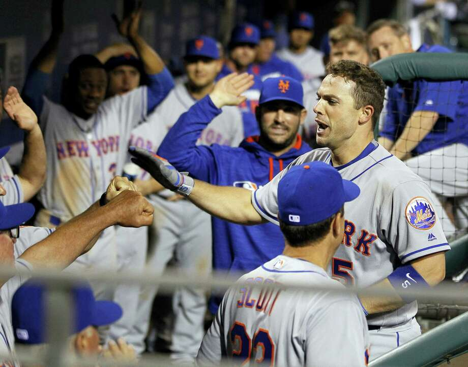 David Wright is greeted in the dugout with high fives after his second homer of the night during the ninth inning of the New York Mets' 5-2 victory over the Philadelphia Phillies on Monday night in Philadelphia. Photo: TOM MIHALEK - THE ASSOCIATED PRESS  / FR148949 AP