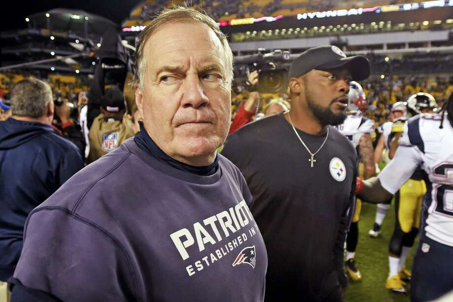 Patriots head coach Bill Belichick, left, heads to his locker room after shaking hands with Steelers head coach Mike Tomlin after Sunday's game. Photo: Don Wright — The Associated Press  / FR87040 AP