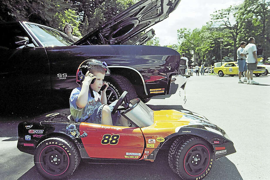 A Middletown 4-year-old adjusts his helmet in the little sportscar his father made for him. His father's toy, a 1970 Chevelle SS, is on display next to him during Tuscany Grill's sixth annual car show in 2001. Photo: File Photo