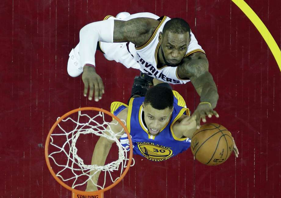 The Warriors' Stephen Curry, bottom, drives to the basket against the Cavaliers' LeBron James during Game 6 of the NBA Finals on Thursday. The two will face off in a rare Game 7 tonight in Oakland, Calif. Photo: Ron Schwane — The Associated Press  / AP 2016