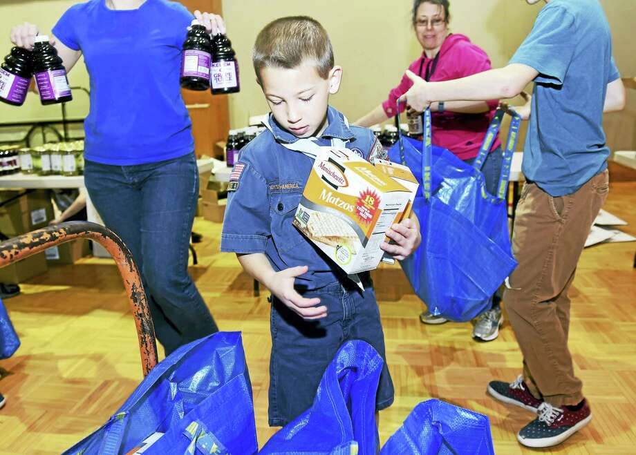 Seth Glassman, 9, of Cub Scout Pack 923 in Orange places boxes of matzo into kosher for Passover food packages for some of over 380 area families at the Jewish Community Center of Greater New Haven in Woodbridge on Sunday. B'nai B'rith International organizes Project H.O.P.E. (Help Our People Everywhere) to deliver Passover food to poor and elderly Jews in several Northeastern states. Photo: Arnold Gold — Register