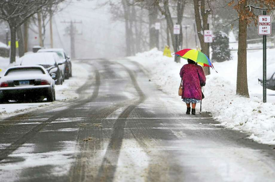 A woman walks in the snowfall down Bradley Avenue in Branford Monday. Schools in Branford were set to open 90 minutes late Tuesday as the town cleaned up from the latest storm. Photo: Peter Hvizdak — New Haven Register  / ©2016 Peter Hvizdak