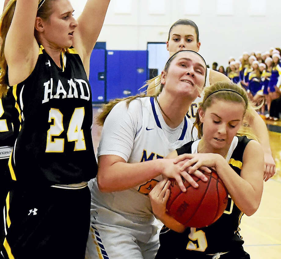 Mercy's Meghan DeVille, center, is tied up by Hand's Emma Sullivan, right, during the first quarter Friday night in Middletown. Photo: Peter Hvizdak - New Haven Register  / ?2016 Peter Hvizdak