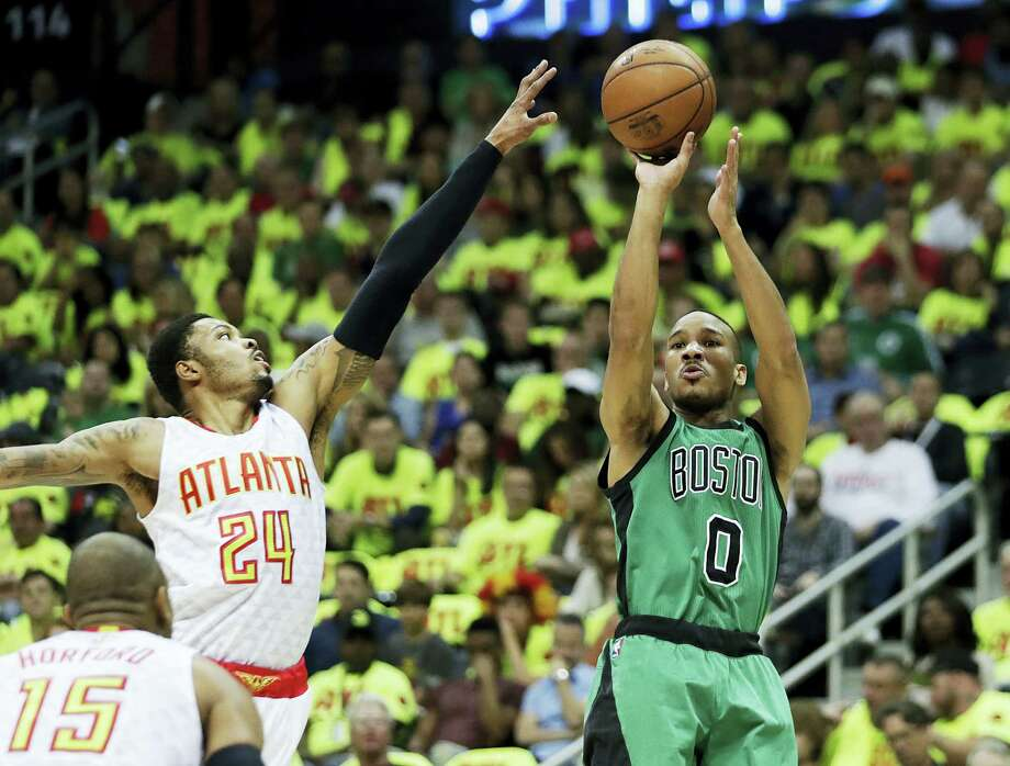 The Celtics' Avery Bradley, right, shoots in front of the Hawks' Kent Bazemore in the first quarter Saturday. Photo: David Goldman — The Associated Press  / Copyright 2016 The Associated Press. All rights reserved. This material may not be published, broadcast, rewritten or redistributed without permission.