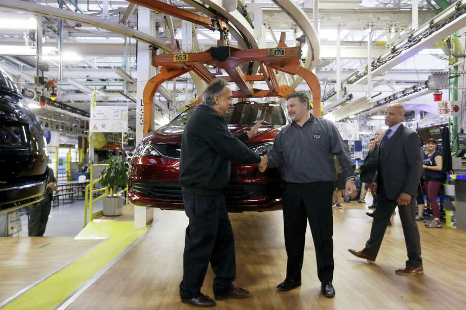 Fiat Chrysler Automobiles Chairman and CEO Sergio Marchionne, left, shakes hands with Dino Chiodo, president of Unifor Local 444, in front of a 2017 Pacifica minivan on the Windsor Assembly Plant line, in Windsor, Ontario. Fiat Chrysler and Google are working together to more than double the size of Google's self-driving vehicle fleet by adding 100 Chrysler Pacifica minivans. Photo: Carlos Osorio — The Associated Press  / Copyright 2016 The Associated Press. All rights reserved. This material may not be published, broadcast, rewritten or redistribu