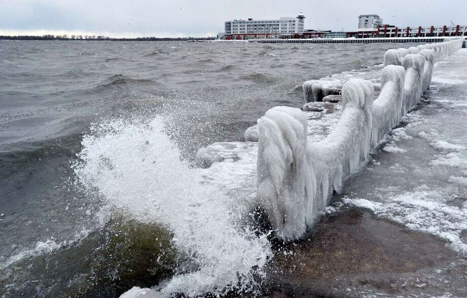 Waves crash along frozen abutments and fencing Thursday, Dec. 15, 2016 on Presque Isle Bay in Erie, Pa. Much of the northern Mid-Atlantic and Northeast will stay cold for the next couple of days as the arctic air remains stuck over the northern Appalachians, the National Weather Service said. Photo: Christopher Millette — Erie Times-News Via AP / Erie Times-News